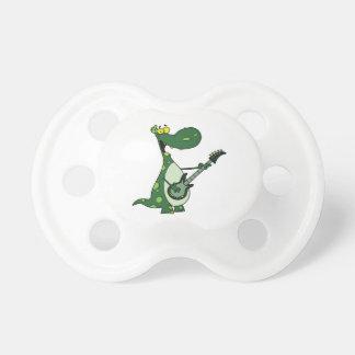 grön grafisk dino hållande gitarr napp