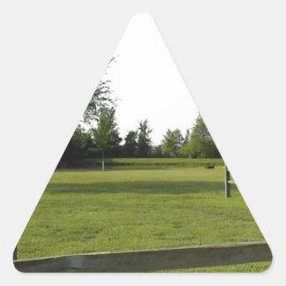 Grön gräsmatta med det Wood staket och träd Triangelformat Klistermärke