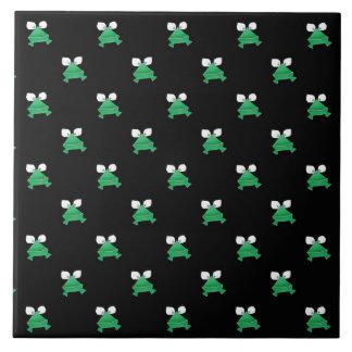 Gröna grodor på svart keramiskt belägger med tegel kakelplatta