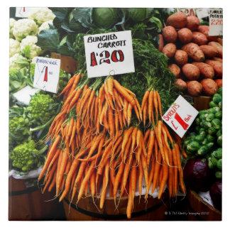 Grupper av morötter och grönsaker marknadsför på kakelplatta
