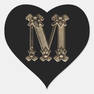 Guld- initialt foto för brev M på svart bakgrund Hjärtformat Klistermärke