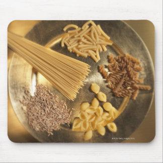 Guld pläterar med pasta och korn av vete musmatta