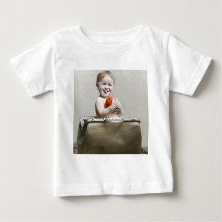 Gullig lite persika för hungrig baby i t shirt
