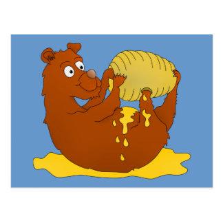 Gullig tecknadbjörn som äter honung vykort