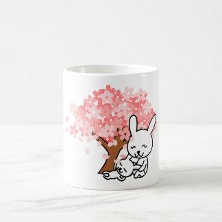 Gulliga kaniner under den körsbärsröda muggen för kaffemugg