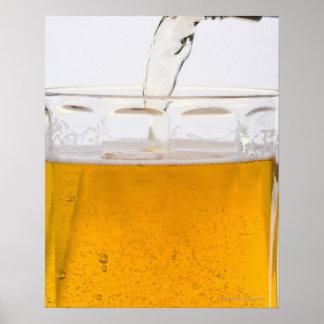 Hällande öl i den glass muggen, ytterlighet, poster