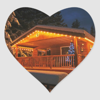 Härligt julljus loggar på kabinen i snö hjärtformat klistermärke