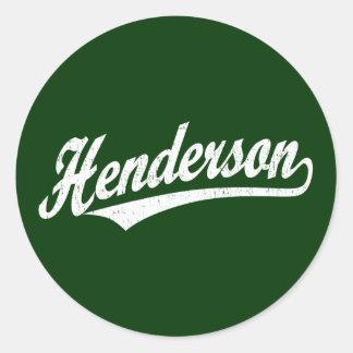 Henderson skrivar logotypen i bedrövad vit runt klistermärke