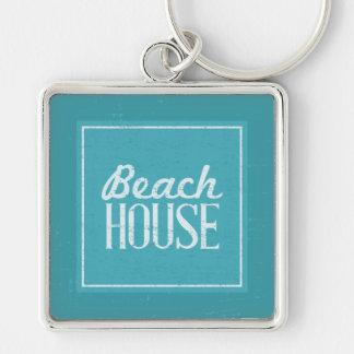Hus för strand för vintageturkosblått fyrkantig silverfärgad nyckelring