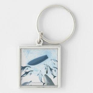Illustrationen av delfiner tittar upp på ett fyrkantig silverfärgad nyckelring