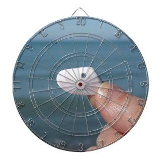 Innehav ett snäckskal i räcka med blåtthavet darttavla