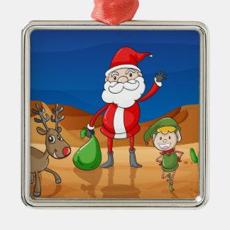 jultomten och en ren silverfärgad fyrkantigt julgransprydnad