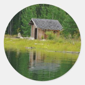 Kabin reflekterad i berg sjön runt klistermärke
