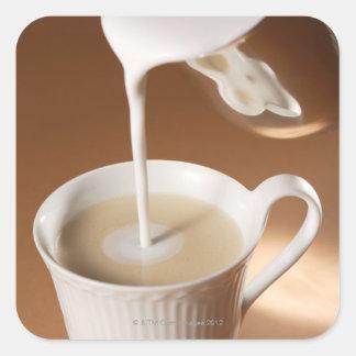 Kaffe med mjölk som in hälls fyrkantigt klistermärke
