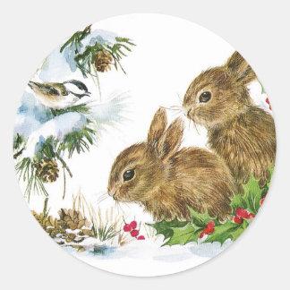 Kaniner och fågeln tycker om snö runt klistermärke