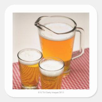 Kannan av öl och två exponeringsglas fyllde med öl fyrkantigt klistermärke