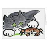Kattungen har funnit en krabba på stranden hälsnings kort