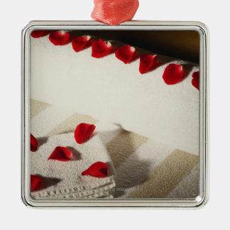 Kickvinkeln beskådar av rosa petals på handdukar julgransprydnad metall