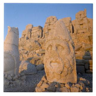 Kolossala head statyer av gudar bevaka kakelplatta