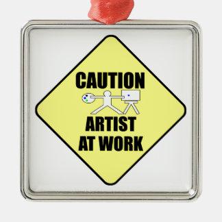 konstnären på arbete undertecknar julgransprydnad metall
