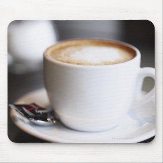 kopp av kaffelatte på bord, närbild musmatta