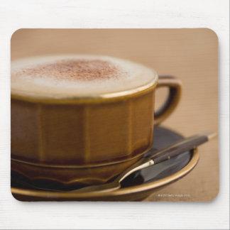 Koppen av cappuccino med kakao pudrar musmatta