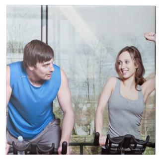 Kvinna på motionscykelen som triumferar över man kakelplatta