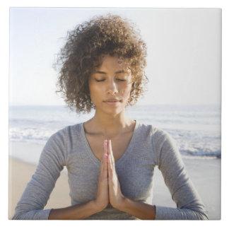Kvinna som gör yoga på strand kakelplatta