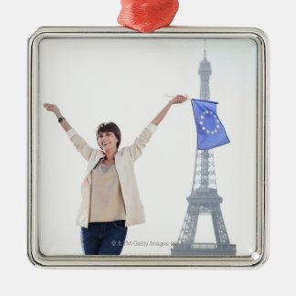 Kvinnainnehav en Europeiska unionflagga och en Julgransprydnad Metall