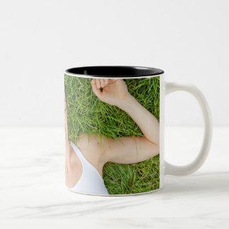 Kvinnan kopplar av med musik i mjukt gräs Två-Tonad mugg