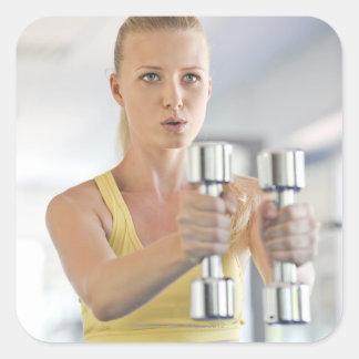 Kvinnan som övar med, väger fyrkantigt klistermärke