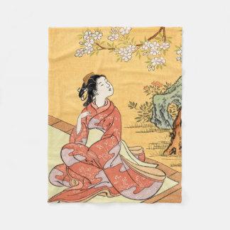 Kvinnasitta under körsbärsröda blommar fleecefilt