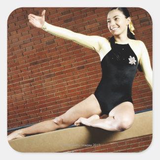 Kvinnlig gymnast som övar på en balansbom och fyrkantigt klistermärke