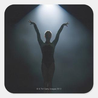 Kvinnlig gymnast som utför i strålkastaren, studio fyrkantigt klistermärke