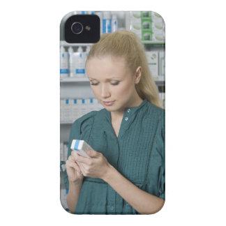 Kvinnlig pharmacist tittar medicin i 2 iPhone 4 hud