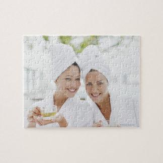 Kvinnor i badrockar som dricker tea på brunnsorten jigsaw puzzles