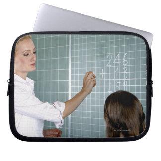 lärare och ung flicka framme av blackboarden in laptop sleeve