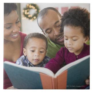 Läs- bok för svart familj tillsammans kakelplatta