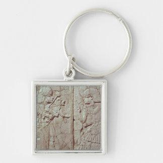 Lättnad som visar ett vaktinnehav fyrkantig silverfärgad nyckelring