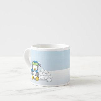 Lite kastar snöboll pingvinsitta med espressomugg