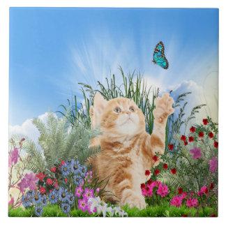 Ljust rödbrun kattunge som leker med en fjäril kakelplatta