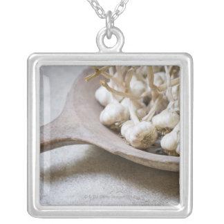 Lökar av vitlök i en lergodsbunke silverpläterat halsband