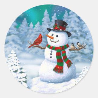 Lyckliga snögubbe- och vinterfåglar runt klistermärke