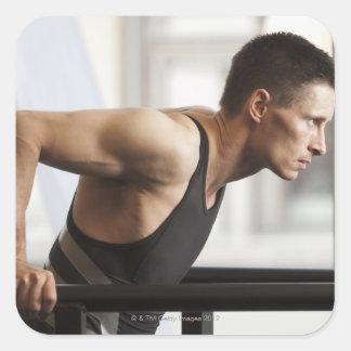 Male idrottsman som använder gymnastikutrustning i fyrkantigt klistermärke