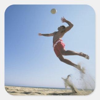 Male strandvolleybollspelare som upp till hoppar fyrkantigt klistermärke