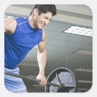 Man i idrottshallen, lyftande stor skivstång som fyrkantigt klistermärke