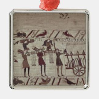 Manar som bär ärmar till frakterna och drar a silverfärgad fyrkantigt julgransprydnad