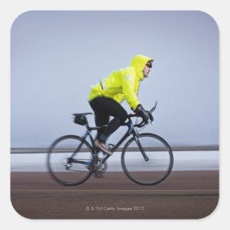 Manen cyklar på en kall och en dimmig vinterdag fyrkantigt klistermärke