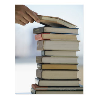 Manen räcker att ta en bok från en bunt av bokar vykort