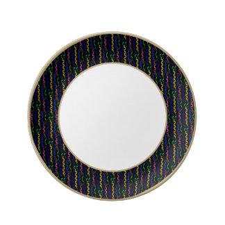 Mång--färgade partybanderoller på en svart porslinstallrik